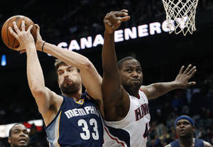 Photo - Memphis Grizzlies center Marc Gasol (33) pulls down a rebound against Atlanta Hawks power forward Elton Brand (42) in the first half of an NBA basketball game Saturday, Feb. 8, 2014, in Atlanta.  (AP Photo/John Bazemore)