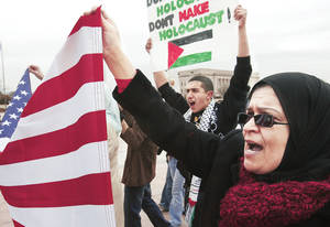 Photo - Malaka Elyazgi of Norman carries the American flag as she marches Monday outside the state Capitol to protest Israel's military offensive against Gaza Strip's Hamas rulers. BY JIM BECKEL, THE OKLAHOMAN
