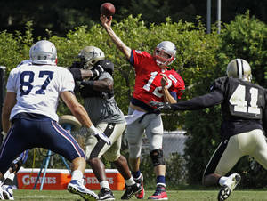 Photo -   New England Patriots quarterback Tom Brady (12) throws a pass to tight end Rob Gronkowski (87) as New Orleans Saints defensive back Roman Harper (41) closes in during a joint NFL football practice in Foxborough, Mass., Tuesday, Aug. 7, 2012. (AP Photo/Stephan Savoia)