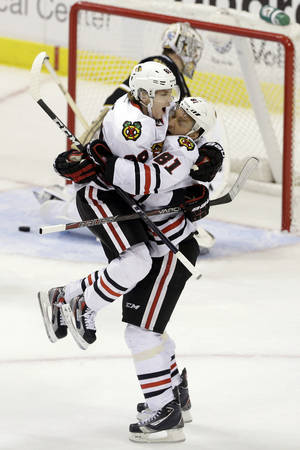 photo - Chicago Blackhawks' Patrick Kane is lifted by Marian Hossa (81), of Slovakia , as they celebrate Hossa's overtime goal against Dallas Stars goalie Kari Lehtonen, rear, of Finland, during an NHL hockey game, Thursday, Jan. 24, 2013, in Dallas. The Blackhawks won 3-2. (AP Photo/Tony Gutierrez)