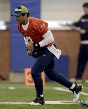 Photo - Seattle Seahawks quarterback Russell Wilson warms up during NFL football practice Friday, Jan. 31, 2014, in East Rutherford, N.J. The Seahawks and the Denver Broncos are scheduled to play in the Super Bowl XLVIII football game Sunday, Feb. 2, 2014. (AP Photo/Jeff Roberson)