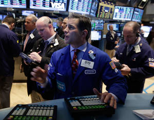 Photo - FILE - In this Friday, Jan. 10, 2014, file photo, specialist Anthony Rinaldi, center, works on the floor of the New York Stock Exchange. Investors are hoping Wall Street will have a better day on Tuesday, Jan. 14, 2014, following the market's worst day of the year so far. Stocks dropped Monday as falling oil prices pushed down energy stocks. (AP Photo/Richard Drew, File)