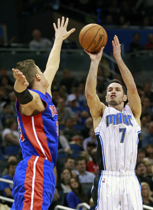 Photo - FILE - In this Nov. 21, 2012 file photo, Orlando Magic's J.J. Redick (7) takes a 3-point shot over the arms of Detroit Pistons' Jonas Jerebko, of Sweden, during the second half of an NBA basketball game in Orlando, Fla. A person familiar with the situation says the Orlando Magic have agreed to trade veteran shooting guard Redick, center Gustavo Ayon and reserve point guard Ish Smith to the Milwaukee Bucks in exchange for guards Doron Lamb and Beno Udrih, as well as forward Tobias Harris. The person spoke to The Associated Press Thursday, Feb. 21, 2013 on condition of anonymity because the deal was not officially complete. (AP Photo/John Raoux, File)