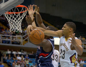 Photo - New Orleans Pelicans power forward Anthony Davis (23) blocks a shot of Atlanta Hawks power forward Paul Millsap (4) in a NBA preseason basketball game between the New Orleans Pelicans and the Atlanta Hawks in Biloxi, Miss. Sunday, Oct. 13, 2013.  (AP Photo/Matthew Hinton)