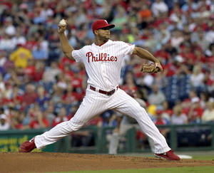 Photo - Philadelphia Phillies pitcher Luis Garcla  throws against the Arizona Diamondbacks in the first inning of a baseball game, Saturday, Aug. 24, 2013, in Philadelphia. (AP Photo/H. Rumph Jr)