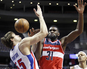 Photo - Detroit Pistons center Viacheslav Kravtsov, left, steals the ball from Washington Wizards forward Chris Singleton (31) in the first half of an NBA basketball game Wednesday, Feb. 13, 2013, in Auburn Hills, Mich. (AP Photo/Duane Burleson)
