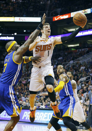 Photo - Phoenix Suns' Goran Dragic (1), of Slovenia, drives past Golden State Warriors' Jermaine O'Neal (7) to score as Warriors' Andre Iguodala, right, stands near during the second half of an NBA basketball game Saturday, Feb. 8, 2014, in Phoenix. The Suns won 122-109. (AP Photo/Ross D. Franklin)