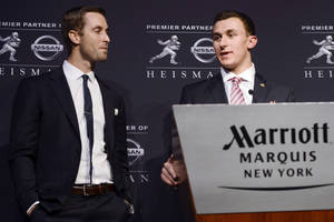 Photo - FILE - In this Dec. 8, 2012, file photo, Texas A&M offensive coordinator Kliff Kingsbury, left, watches as quarterback Johnny Manziel speaks after becoming the first freshman to win NCAA college football's Heisman Trophy in New York. Kingsbury was hired Wednesday, Dec. 12, as the new head coach of Texas Tech, where he was the first in a string of record-setting quarterbacks under former coach Mike Leach. (AP Photo/Henny Ray Abrams, File)