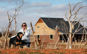 Photo - Tiffany Johnson and her pet rottweiler, Dutchess, are a few hundred yards south of the home she and her husband, Duane, are rebuilding near Waterloo and Sara roads. Their previous home was destroyed in an EF-5 tornado in May.  Photo by Jim Beckel, The Oklahoman