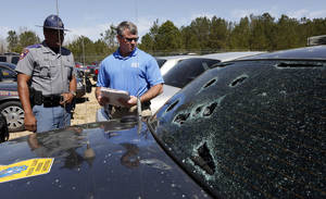 Photo - Mississippi Highway Patrol Lt. Col. Mike Holmes, right, and Cpl. Odis Easterling, survey the damage made by hail stones to a crusier, Monday, March 19, 2013 in Pearl, Miss. Some 65 Highway Patrol fleet backup vehicles were severely damaged by Monday's hail storm, as were a number of other service vehicles in central Mississippi. Authorities say it's too early to know exactly how many structures and vehicles were damaged, but it appears to be widespread in parts of Jackson and its suburbs, with hail reported as big as baseballs pounding some spots. (AP Photo/Rogelio V. Solis)