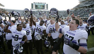 Photo -   Northwestern players celebrate their 23-20 win over Michigan State in an NCAA college football game, Saturday, Nov. 17, 2012, in East Lansing, Mich. (AP Photo/Al Goldis)