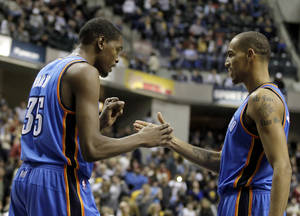 Photo - Thunder forward Kevin Durant, left, and Thabo Sefolosha react in overtime against the Pacers on Friday. AP PHOTO