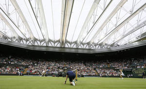 Photo - The roof is closed on Centre Court as Agnieszka Radwanska of Poland, right, plays Mathilde Johansson of France during their Women's second round singles match at the All England Lawn Tennis Championships in Wimbledon, London, Thursday, June 27, 2013. (AP Photo/Kirsty Wigglesworth)