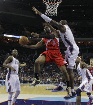 Photo - Los Angeles Clippers' Chris Paul, center, shoots as Charlotte Bobcats' Bismack Biyombo, right, and Kemba Walker, left, defend during the first half of an NBA basketball game in Charlotte, N.C., Wednesday, Dec. 12, 2012. (AP Photo/Chuck Burton)