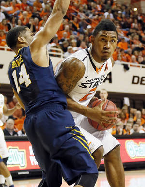 Photo - Oklahoma State's Le'Bryan Nash (2) works against West Virginia's Gary Browne (14) during an NCAA men's basketball game between Oklahoma State University (OSU) and West Virginia at Gallagher-Iba Arena in Stillwater, Okla., Saturday, Jan. 26, 2013. Photo by Nate Billings, The Oklahoman