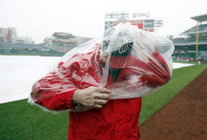 Photo - Bob Coleman, with field security, puts on his rain poncho before an exhibition baseball game between the Washington Nationals and the Detroit Tigers at Nationals Park Saturday, March 29, 2014, in Washington. The game was canceled due to weather. (AP Photo/Alex Brandon)