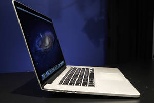 photo -   This Wednesday, June 13, 2012 photo shows a profile view of the new 15-inch MacBook Pro with Retina display, in New York. The new laptop features a display that has four times as many pixels as a standard display. The Retina MacBook starts at $2199, nearly three times as much as the average consumer spends on a laptop, but it isn't a bad price for the video editors, photographers and graphic designers who are the intended buyers. Compared to the regular MacBook model, it's thinner, lighter and lacks a DVD drive. It even lacks an Ethernet port for Internet connections. (AP Photo/Kathy Willens)