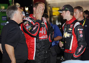 Photo - Driver Kurt Busch, right, talks to a crew member, center, and team owner Carl Haas, left, after dropping out of the NASCAR Sprint Cup series Coca-Cola 600 auto race at Charlotte Motor Speedway in Concord, N.C., Sunday, May 25, 2014. (AP Photo/Terry Renna)