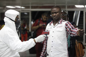 Photo - FILE - In this Aug. 6, 2014 file photo, a Nigerian port health official uses a thermometer on a worker at the arrivals hall of Murtala Muhammed International Airport in Lagos, Nigeria. As the Ebola outbreak in West Africa grows, airlines around the globe are closely monitoring the situation but have yet to make any drastic changes. (AP Photo/Sunday Alamba, File)