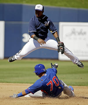 Photo - Milwaukee Brewers' Jean Segura leaps over Chicago Cubs' Javier Baez (70) as he tries to turn a double play on a ball hit by Aaron Cunningham during the fourth inning of an exhibition spring training baseball game Monday, March 3, 2014, in Phoenix. Cunningham beat the throw to first. (AP Photo/Morry Gash)