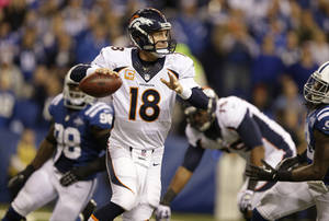 Photo - Denver Broncos quarterback Peyton Manning (18) scrambles during the second half of an NFL football game against the Indianapolis Colts, Sunday, Oct. 20, 2013, in Indianapolis. (AP Photo/Michael Conroy)