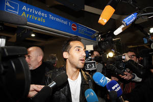 Photo - French Algerian football player Zahir Belounis is surrounded by cameras as he arrives from Qatar at Roissy Charles De Gaulle airport, north of Paris, France, Thursday, Nov. 28, 2013. Belounis said he was stranded in Qatar with his wife and their two daughters. He was refused the exit visa he needed to leave because of a legal dispute over unpaid wages with Qatari side Al-Jaish, where he was under contract until 2015. (AP Photo/Francois Mori)