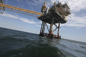 photo - In this Tuesday, April 27, 2010, file photo, an oil rig is seen in the Gulf of Mexico near the Chandeleur Islands, off the Southeastern tip of Louisiana. Energy companies have reoccupied nearly 400 of the production platforms in the Gulf of Mexico that were abandoned in advance of Hurricane Isaac, though oil production remains almost entirely shut down. Oil and gas workers began retaking the offshore sites Friday and federal officials on Saturday, Sept. 1, 2012 say that 377 of the 596 productions platforms have some staffing on them, up from just 97. AP file photo <strong>Gerald Herbert - AP</strong>