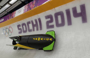 Photo - The JAM-1 sled from Jamaica, takes a turn during a training run for the men's two-man bobsled at the 2014 Winter Olympics, Thursday, Feb. 6, 2014, in Krasnaya Polyana, Russia. (AP Photo/Michael Sohn)