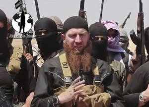 Photo - This image made from undated video posted during the weekend of June 28, 2014 on a social media account frequently used for communications by the Islamic State of Iraq and the Levant (ISIL), which has been verified and is consistent with other AP reporting, shows Omar al-Shishani standing next to the group's spokesman among a group of fighters as they declare the elimination of the border between Iraq and Syria. Al-Shishani, one of hundreds of Chechens who have been among the toughest jihadi fighters in Syria, has emerged as the face of the Islamic State of Iraq and the Levant, appearing frequently in its online videos — in contrast to the group's Iraqi leader, Abu Bakr al-Baghdadi, who remains deep in hiding and has hardly ever been photographed. (AP Photo/militant social media account via AP video)