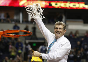 Photo - Connecticut head coach Geno Auriemma holds the net after the second half of the championship game against Notre Dame in the Final Four of the NCAA women's college basketball tournament, Tuesday, April 8, 2014, in Nashville, Tenn. Connecticut won 79-58. (AP Photo/John Bazemore)
