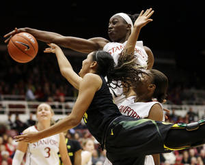 Photo - Stanford 's Chiney Ogwumike, top, blocks a layup-attempt from Oregon's Lexi Petersen during the first half of an NCAA college basketball game on Friday, Jan. 3, 2014, in Stanford, Calif. (AP Photo/Marcio Jose Sanchez)