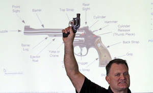 "Photo - FILE - In this Dec. 27, 2012, file photo, Clark Aposhian, president of Utah Shooting Sport Council, holds a pistol during concealed weapons training for 200 Utah teachers, in West Valley City, Utah, with a diagram of gun parts projected behind him. Utah's top gun lobbyist will once again be able to access his arsenal after resolving a criminal case against him. On Monday, June 23, 2014, Aposhian pleaded no contest to a disorderly conduct infraction stemming from honking a horn, and was ordered to pay a $320 fine. His lawyer says Aposhian feels ""vindicated"" that other counts, including a domestic violence charge, were dismissed. (AP Photo/Rick Bowmer, File)"