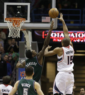 photo - Atlanta Hawks' Al Horford(15) puts up the game-winning shot against Milwaukee Bucks' Larry Sanders during the second half of an NBA basketball game, Saturday, Feb. 23, 2013, in Milwaukee. Atlanta won 103-102. (AP Photo/Jeffrey Phelps)