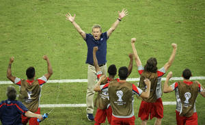 Photo - United States' head coach Juergen Klinsmann celebrates after his team won 2-1 during the group G World Cup soccer match between Ghana and the United States at the Arena das Dunas in Natal, Brazil, Monday, June 16, 2014. (AP Photo/Hassan Ammar)