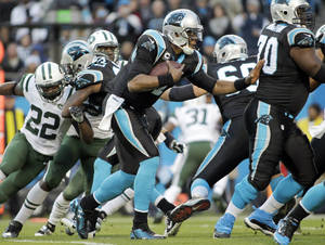 Photo - Carolina Panthers' Cam Newton, center, rushes for a first down against the New York Jets during the first half of an NFL football game in Charlotte, N.C., Sunday, Dec. 15, 2013. (AP Photo/Bob Leverone)
