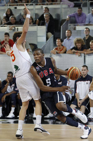 photo - Kevin Durant, right, drives with the ball past Spain's Rudy Fernandez during Sunday's game. AP PHOTO