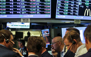 Photo -   FILE- In a July 13, 2012, file photo, traders work as the New York Stock Exchange nears closing. JPMorgan Chase blew away a cloud of concern hanging over the banking industry Friday and set off a rally in stocks. (AP Photo/Bebeto Matthews)