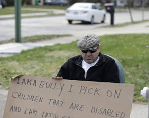 "Photo - Edmond Aviv sits on a street corner holding a sign Sunday, April 13, 2014, in South Euclid, Ohio declaring he's a bully, a requirement of his sentence because he was accused of harassing a neighbor and her disabled children for the past 15 years.  Municipal Court Judge Gayle Williams-Byers ordered Aviv, 62,  to display the sign for five hours Sunday. It says: ""I AM A BULLY! I pick on children that are disabled, and I am intolerant of those that are different from myself. My actions do not reflect an appreciation for the diverse South Euclid community that I live in."" (AP Photo/Tony Dejak)"
