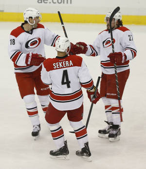 Photo - Carolina Hurricanes' Justin Faulk (27) celebrates scoring a goal with teammates Andrej Sekera (4), and Radek Dvorak (18), of the Czech Republic, during the first period of an NHL hockey game against the Pittsburgh PenguinsonTuesday, April 1, 2014, in Pittsburgh. (AP Photo/Keith Srakocic)