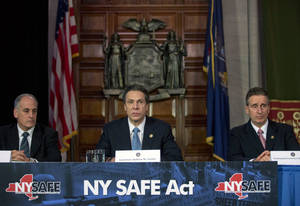 photo - New York Gov. Andrew Cuomo, center, speaks during a news conference announcing an agreement with legislative leaders on New York's Secure Ammunition and Firearms Enforcement Act in the Red Room at the Capitol on Monday, Jan. 14, 2013, in Albany, N.Y. Also pictured are Secretary to the Governor Larry Schwartz, left, and Lt. Gov. Robert Duffy. (AP Photo/Mike Groll)