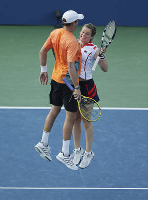 Photo -   Belgium's Kim Clijsters, right, and Bob Bryan celebrate after their mixed doubles match against Irina Falconi and Steve Johnson in the third round of play at the 2012 US Open tennis tournament, Friday, Aug. 31, 2012, in New York. (AP Photo/Charles Krupa)