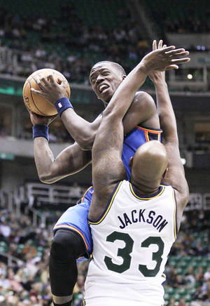 Photo - Thunder guard Reggie Jackson, top, drives to the basket as Jazz forward Darnell Jackson defends in the second quarter during a preseason game on Friday. AP Photo