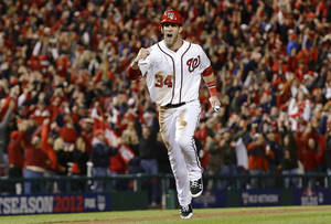 Photo -   Washington Nationals' Bryce Harper heads home on a home run by Ryan Zimmerman during the first inning of Game 5 of the National League division baseball series against the St. Louis Cardinals on Friday, Oct. 12, 2012, in Washington. (AP Photo/Alex Brandon)