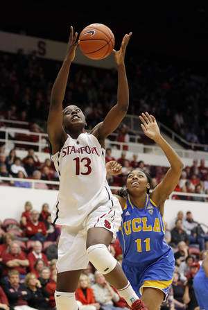 Photo - Stanford 's Chiney Ogwumike (13) grabs a lob pass in front of UCLA 's Atonye Nyingifa (11) during the first half of an NCAA college basketball game Friday, Jan. 24, 2014, in Stanford, Calif. (AP Photo/Marcio Jose Sanchez)