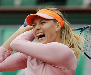 Photo - Russia's Maria Sharapova returns the ball to Bulgaria's Tsvetana Pironkova during the second round match of  the French Open tennis tournament at the Roland Garros stadium, in Paris, France, Wednesday, May 28, 2014. (AP Photo/David Vincent)