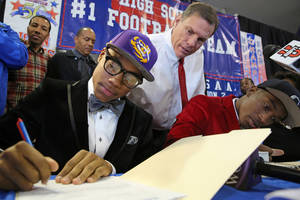Photo - John Curtis head football coach J.T. Curtis, left, watches as Malachi Dupre signs his letter of intent for LSU at the John Curtis High School gym on National Signing Day, Wednesday, Feb. 5, 2014. (AP Photo/The Times-Picayune, Julia Kumari Drapkin)