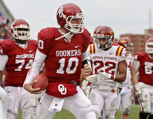 Photo - Iowa State safety Ter'Ran Benton (22) looks on as Oklahoma quarterback Blake Bell celebrates a touchdown in the second quarter of an NCAA college football game in Norman, Okla., Saturday, Nov. 26, 2011. (AP Photo/Sue Ogrocki) ORG XMIT: OKSO105