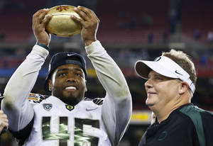 Photo - Oregon's Michael Clay, left, holds up the championship trophy as head coach Chip Kelly looks on after the Fiesta Bowl NCAA college football game against Kansas State Thursday, Jan. 3, 2013, in Glendale, Ariz.  Oregon defeated Kansas State 35-17.(AP Photo/Ross D. Franklin)