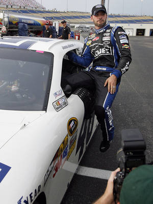 Photo -   Jimmie Johnson steps from his car after securing the pole position for Saturday's NASCAR Sprint Cup Series auto race at Kentucky Speedway in Sparta, Ky., Friday, June 29, 2012. (AP Photo/James Crisp)
