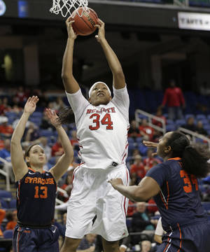Photo - North Carolina State's Markeisha Gatling, center, shoots between Syracuse's Brianna Butler, left, and Shakeya Leary, right, during the first half of an NCAA college basketball game at the Atlantic Coast Conference tournament in Greensboro, N.C., Friday, March 7, 2014. (AP Photo/Chuck Burton)
